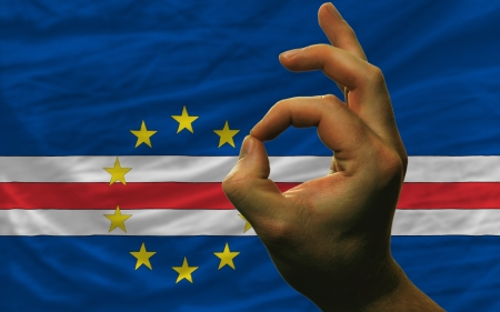 man showing excellence or ok gesture in front of complete wavy capeverde national flag of  symbolizing best quality, positivity and succes Stock Photo - 14428315