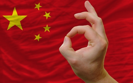 man showing excellence or ok gesture in front of complete wavy china national flag of  symbolizing best quality, positivity and succes photo