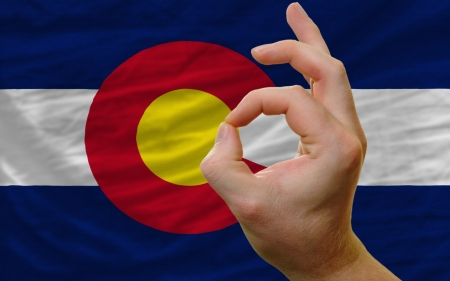 man showing excellence or ok gesture in front of complete wavy american state flag of colorado symbolizing best quality, positivity and succes photo