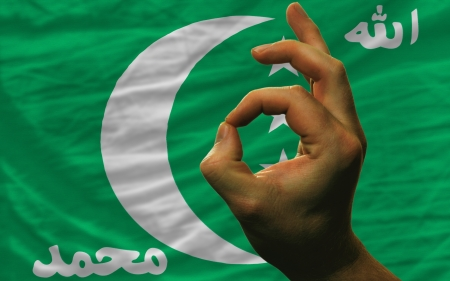 man showing excellence or ok gesture in front of complete wavy comoros national flag of  symbolizing best quality, positivity and succes Stock Photo - 14428529