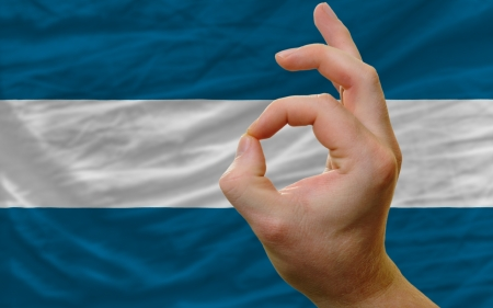 el salvadoran: man showing excellence or ok gesture in front of complete wavy el salvador national flag of  symbolizing best quality, positivity and succes Stock Photo