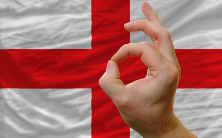 man showing excellence or ok gesture in front of complete wavy england national flag of  symbolizing best quality, positivity and succes photo