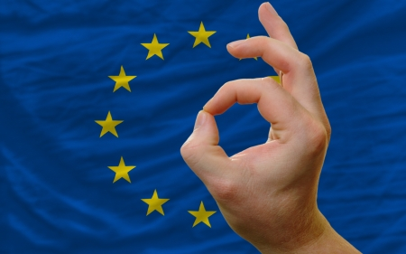 man showing excellence or ok gesture in front of complete wavy europe national flag of  symbolizing best quality, positivity and succes photo