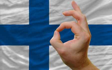 man showing excellence or ok gesture in front of complete wavy finland national flag of  symbolizing best quality, positivity and succes Stock Photo - 14427818
