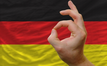 man showing excellence or ok gesture in front of complete wavy germany national flag of  symbolizing best quality, positivity and succes photo
