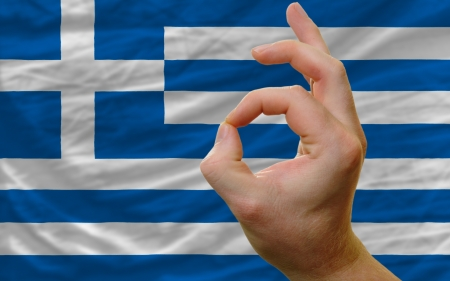 man showing excellence or ok gesture in front of complete wavy greece national flag of  symbolizing best quality, positivity and succes Stock Photo - 14427747