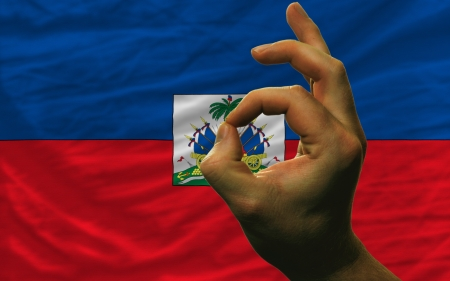 man showing excellence or ok gesture in front of complete wavy haiti national flag of  symbolizing best quality, positivity and succes Stock Photo - 14428524