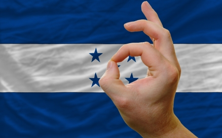 man showing excellence or ok gesture in front of complete wavy honduras national flag of  symbolizing best quality, positivity and succes photo