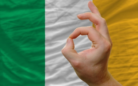 man showing excellence or ok gesture in front of complete wavy ireland national flag of  symbolizing best quality, positivity and succes photo