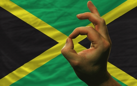 man showing excellence or ok gesture in front of complete wavy jamaica national flag of  symbolizing best quality, positivity and succes Stock Photo - 14428751