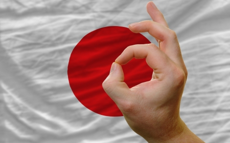 man showing excellence or ok gesture in front of complete wavy japan national flag of  symbolizing best quality, positivity and succes photo
