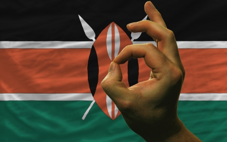 man showing excellence or ok gesture in front of complete wavy kenya national flag of  symbolizing best quality, positivity and succes Stock Photo - 14427767