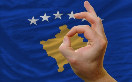 man showing excellence or ok gesture in front of complete wavy kosovo national flag of  symbolizing best quality, positivity and succes photo