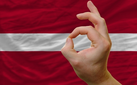 man showing excellence or ok gesture in front of complete wavy latvia national flag of  symbolizing best quality, positivity and succes photo