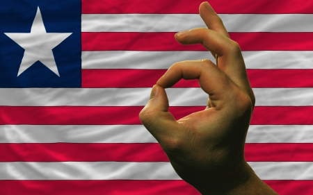man showing excellence or ok gesture in front of complete wavy liberia national flag of  symbolizing best quality, positivity and succes photo