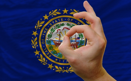 man showing excellence or ok gesture in front of complete wavy american state flag of new hampshire symbolizing best quality, positivity and succes photo
