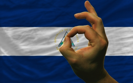 man showing excellence or ok gesture in front of complete wavy nicaragua national flag of  symbolizing best quality, positivity and succes photo