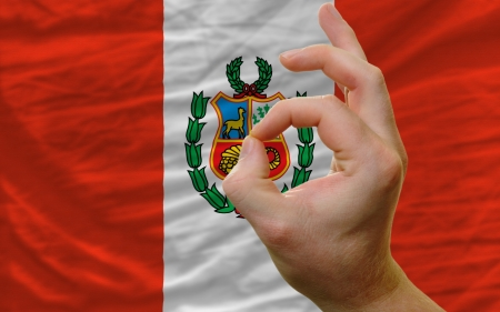 man showing excellence or ok gesture in front of complete wavy peru national flag symbolizing best quality, positivity and succes photo