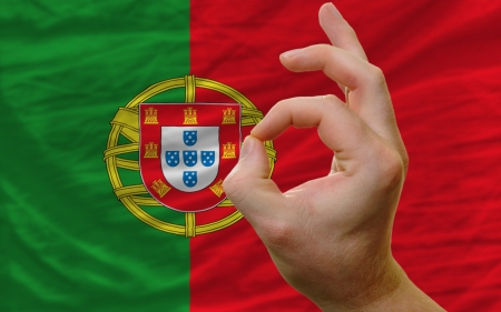 man showing excellence or ok gesture in front of complete wavy portugal national flag of  symbolizing best quality, positivity and succes photo