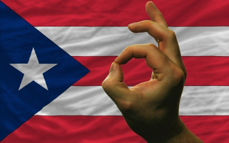 man showing excellence or ok gesture in front of complete wavy puerto rico national flag symbolizing best quality, positivity and succes photo