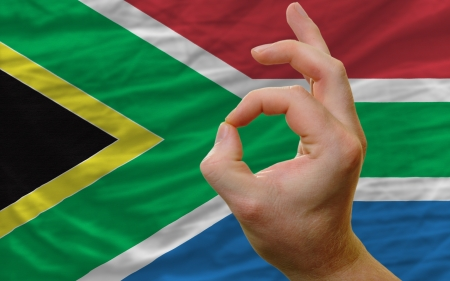 man showing excellence or ok gesture in front of complete wavy south africa national flag symbolizing best quality, positivity and succes photo