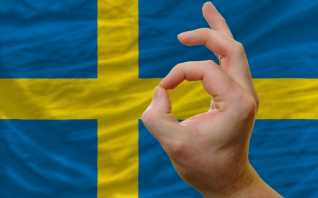 man showing excellence or ok gesture in front of complete wavy sweden national flag symbolizing best quality, positivity and succes Stock Photo - 14428226