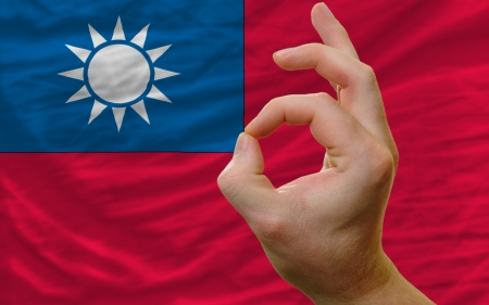 man showing excellence or ok gesture in front of complete wavy taiwan national flag symbolizing best quality, positivity and succes photo