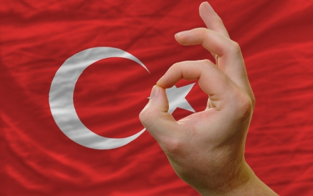 man showing excellence or ok gesture in front of complete wavy turkey national flag of  symbolizing best quality, positivity and succes photo