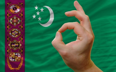 man showing excellence or ok gesture in front of complete wavy turkmenistan national flag of  symbolizing best quality, positivity and succes Stock Photo - 14428653