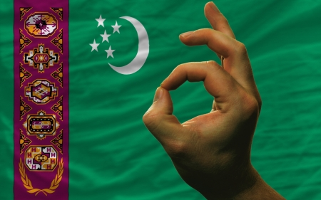 man showing excellence or ok gesture in front of complete wavy turkmenistan national flag of  symbolizing best quality, positivity and succes Stock Photo - 14428630