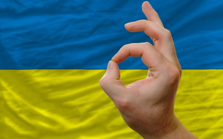 man showing excellence or ok gesture in front of complete wavy ukraine national flag of  symbolizing best quality, positivity and succes Stock Photo