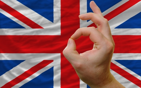 man showing excellence or ok gesture in front of complete wavy great britain national flag of  symbolizing best quality, positivity and succes photo