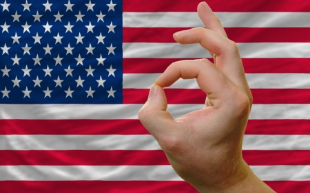 man showing excellence or ok gesture in front of complete wavy america national flag of  symbolizing best quality, positivity and succes photo