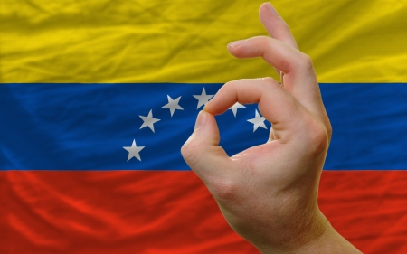 man showing excellence or ok gesture in front of complete wavy venezuela national flag of  symbolizing best quality, positivity and succes photo