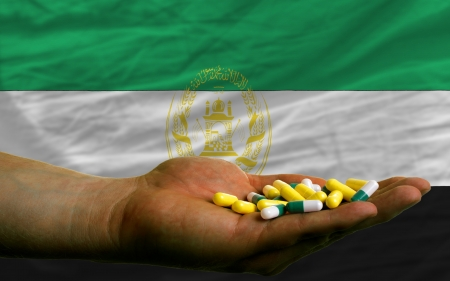 man holding capsules in front of complete wavy national flag of afghanistan symbolizing health, medicine, cure, vitamines and healthy life Stock Photo - 14428146