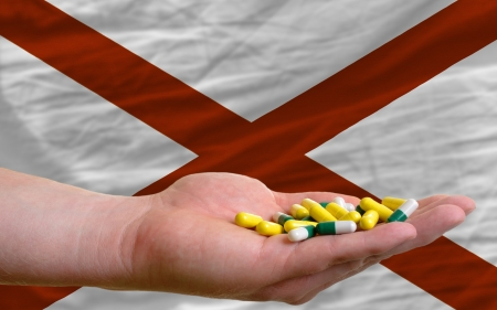 man holding capsules in front of complete wavy american state flag of alabama symbolizing health, medicine, cure, vitamines and healthy life