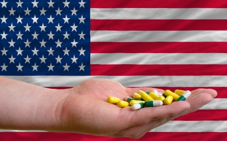 man holding capsules in front of complete wavy american national flag of  symbolizing health, medicine, cure, vitamines and healthy life photo
