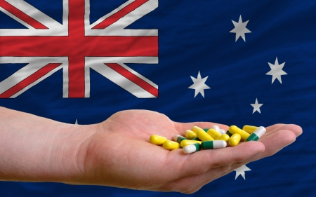 man holding capsules in front of complete wavy national flag of australia symbolizing health, medicine, cure, vitamines and healthy life photo