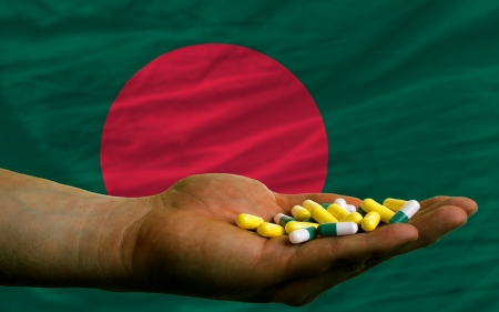 man holding capsules in front of complete wavy national flag of bangladesh symbolizing health, medicine, cure, vitamines and healthy life photo