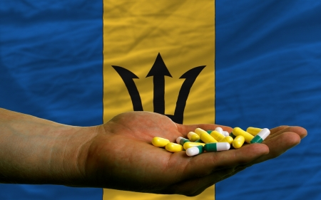 barbadian: man holding capsules in front of complete wavy national flag of barbados symbolizing health, medicine, cure, vitamines and healthy life Stock Photo