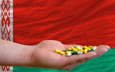 man holding capsules in front of complete wavy national flag of belarus symbolizing health, medicine, cure, vitamines and healthy life Stock Photo - 14428658