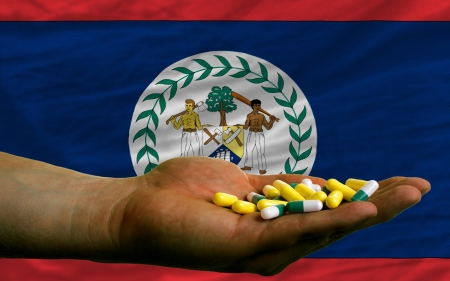 man holding capsules in front of complete wavy national flag of belize symbolizing health, medicine, cure, vitamines and healthy life photo