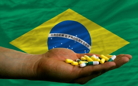 man holding capsules in front of complete wavy national flag of brazil symbolizing health, medicine, cure, vitamines and healthy life photo