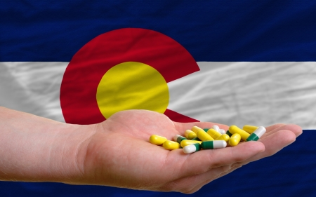 man holding capsules in front of complete wavy american state flag of colorado symbolizing health, medicine, cure, vitamines and healthy life photo