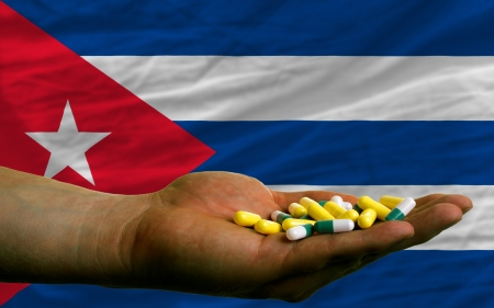 vitamines: man holding capsules in front of complete wavy national flag of cuba symbolizing health, medicine, cure, vitamines and healthy life