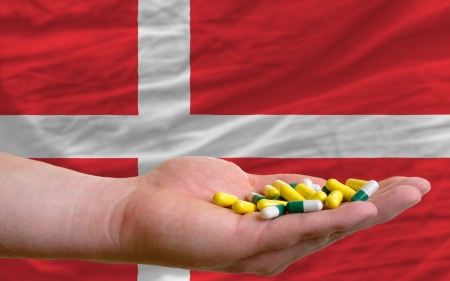 man holding capsules in front of complete wavy national flag of denmark symbolizing health, medicine, cure, vitamines and healthy life photo