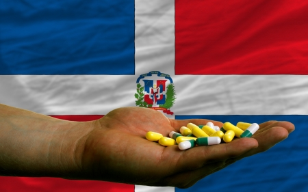 man holding capsules in front of complete wavy national flag of dominican symbolizing health, medicine, cure, vitamines and healthy life photo