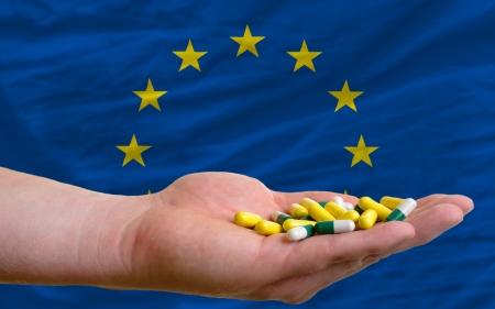 man holding capsules in front of complete wavy national flag of europe symbolizing health, medicine, cure, vitamines and healthy life Standard-Bild