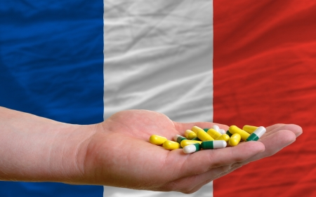 man holding capsules in front of complete wavy national flag of france symbolizing health, medicine, cure, vitamines and healthy life photo