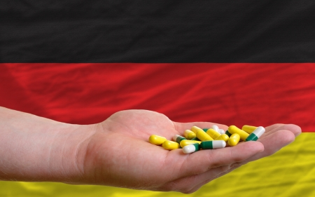 man holding capsules in front of complete wavy national flag of germany symbolizing health, medicine, cure, vitamines and healthy life photo